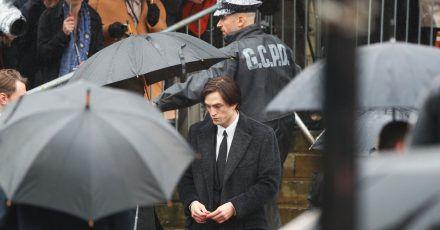 Robert Pattinson steht im Regen.