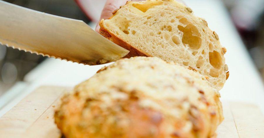 «Fancy-Brot»: Ein Brot mit Kürbis-Käse-Kruste wird in einer Backstube angeschnitten.
