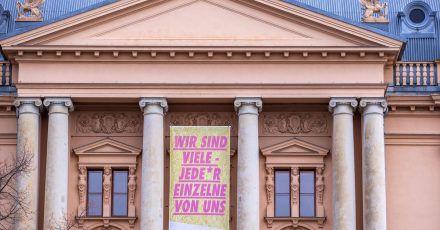 """Ein Transparent mit der Aufschrift """"Wir sind viele - Jeder einzelne von uns""""  am geschlossenen Mecklenburgischen Staatstheater in Schwerin."""