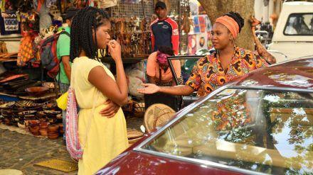 """""""Das Traumschiff: Kapstadt"""" läuft am 26. Dezember 2020 um 20:15 Uhr: Malaika Balewa (Motsi Mabuse) steht in einer offenen Autotür und bietet Lea Bremer (Melodie Wakivuamina) ihre Hand an. (hub/spot)"""