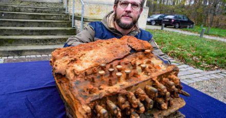Florian Huber, Forschungstaucher, kniet vor dem archäologischen Landesamt Schleswig-Holstein bei der Übergabe der Enigma-Chiffriermaschine, die von ihm in der Ostsee gefunden wurde, neben der Maschine.