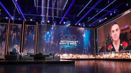 Mit Robbie Williams spricht Thomas Gottschalk in einer Schalte über 2020, Corona und ausgefallene Konzerte. Außerdem stimmt er eines seiner aktuellen Lieder an. (ili/spot)