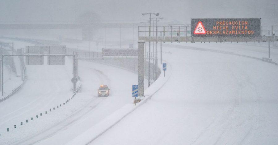 Ein Rettungsfahrzeug fährt auf der leeren, schneebedeckten Schnellstraße M-30 durch Madrid.