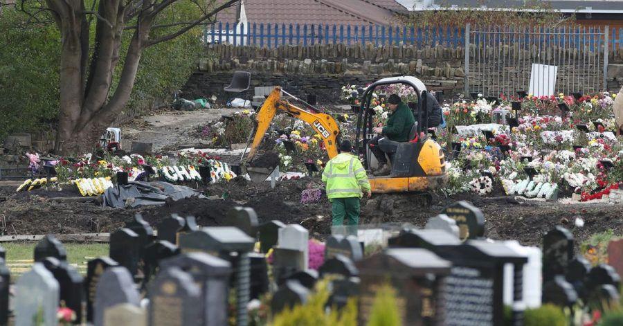 Mitarbeiter heben mit einem Bagger auf einem Friedhof in Nordengland neue Gräber aus.