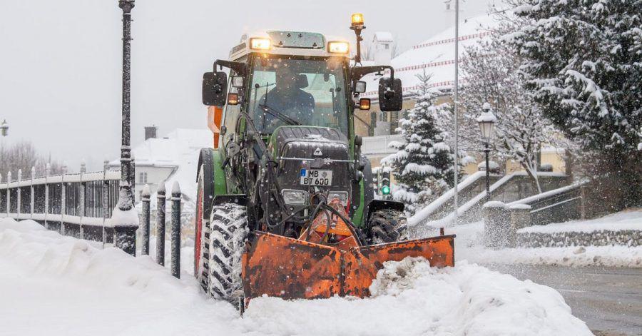 Ein Traktor mit Schneepflug räumt eine verschneite Straße im Ortskern der Ortschaft am Tegernsee.