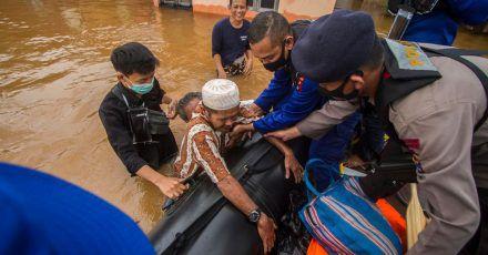 Rettungskräfte helfen einem älteren Mann in einem überfluteten Dorf in ihr Boot.