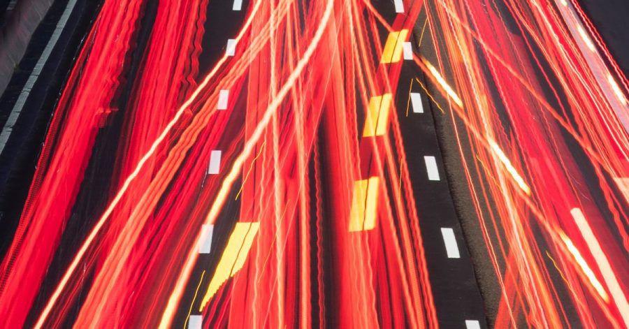 Die Scheinwerfer vorbeifahrender Fahrzeuge ziehen auf einer Autobahn ihre Lichtspuren durch die hereinbrechende Dunkelheit (Aufnahme mit Langzeitbelichtung).