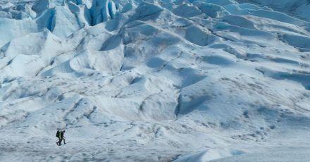 Zwei Menschen wandern auf einem Gletscher in Alaska.