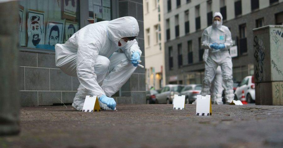 Beamte der Spurensicherung sichern Blutspuren auf dem Gehweg in der Frankfurter Niddastraße.