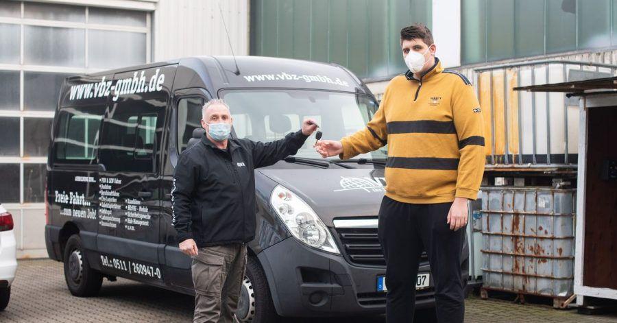 Jannik Könecke (r.) und Jörg Vespermann, Fahrlehrer und Geschäftsführer Berufskraftfahrer-Akademie-Nord GmbH, stehen vor einem für große Fahrschüler umgebauten Fahrzeug.