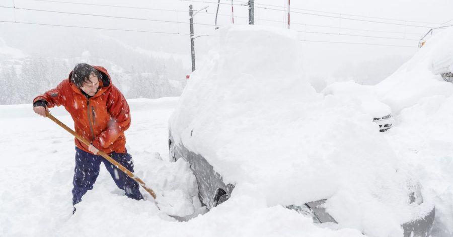 Ein Mann schaufelt sein eingeschneites Auto frei. Viele Walliser Täler sind wegen dem starken Schneefall von der Außenwelt abgeschnitten.