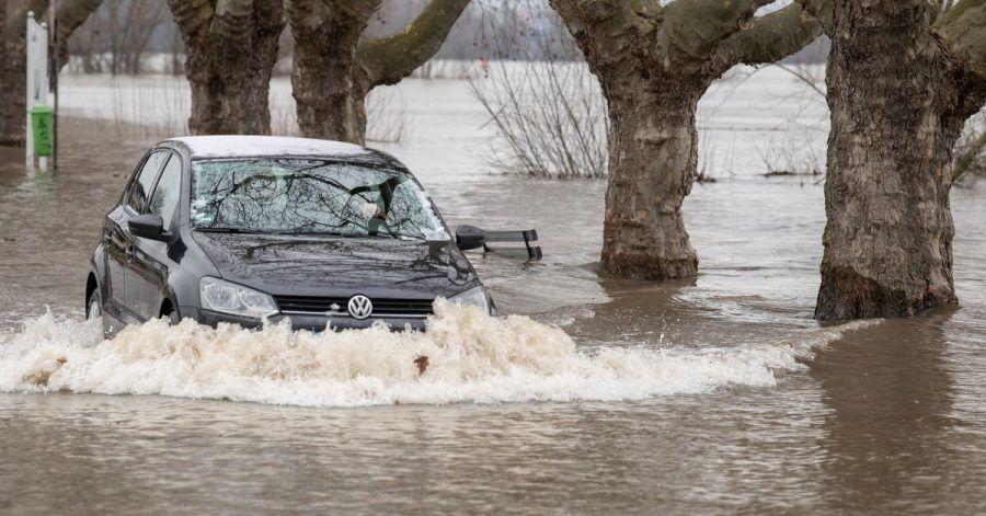 Ein Autofahrer steuert in Rüdesheim am Rhein seinen Wagen über eine vom Hochwasser überflutete Straße.