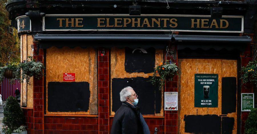 Ein Mann geht an einem geschlossenen Pub in London vorbei.