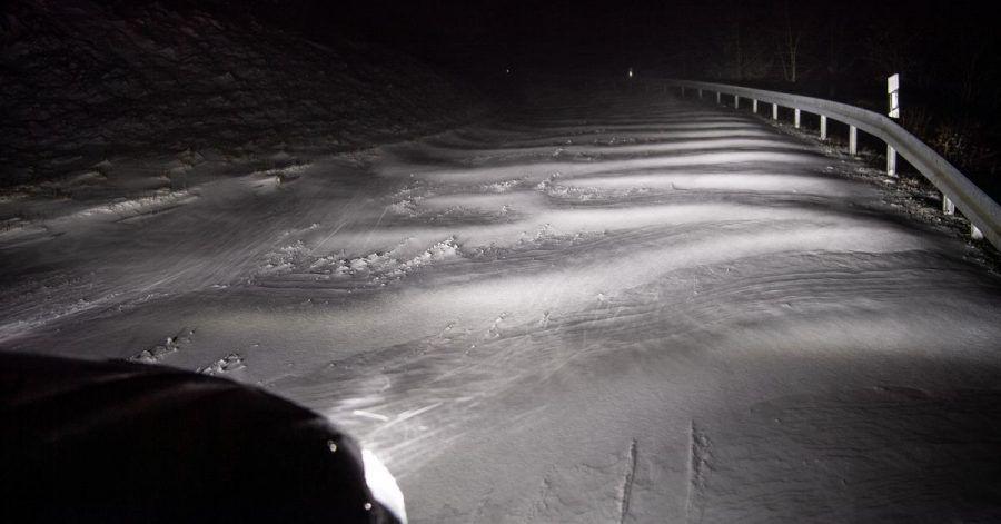 Zugeschneit: Ein Autoscheinwerfer leuchtet Schneeverwehungen auf einer Straße bei Detmold an.