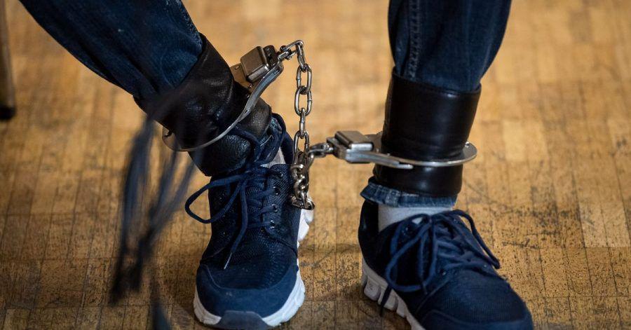 Einer der Angeklagten sitzt mit Fußfessel vor Prozessbeginn in der Stadthalle Verden.