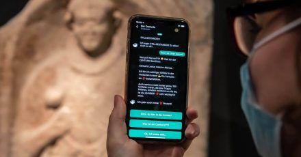Im Badischen Landesmuseum wird vor einem Grabstein eines Centurio aus dem 1. Jahrhundert nach Christus auf einem Smartphone eine App gezeigt, mit der Museumsbesucher Kontakt zu Ausstellungsobjekten aufbauen können.