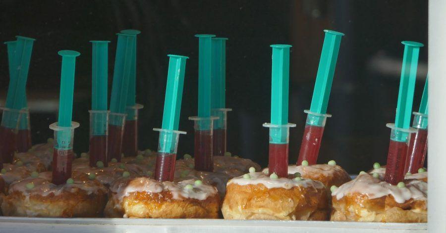 Berliner mit Spritzen, die Erdbeerkonfitüren enthalten, liegen im Schaufenster eines Bäckers in Haan.
