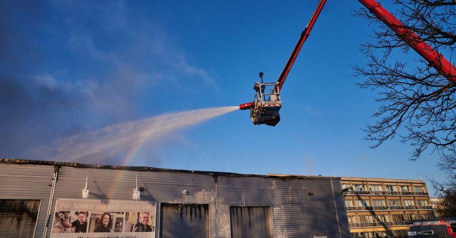 Feuerwehrleute bekämpfen den Brand von einer Drehleiter aus.