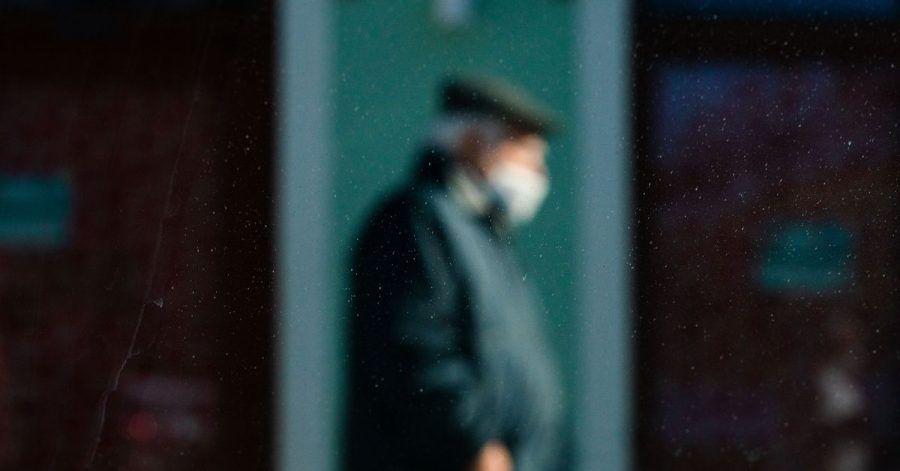Durch eine Scheibe fotografiert, ist ein Mann mit Mund-Nasen-Schutz schemenhaft zu erkennen.