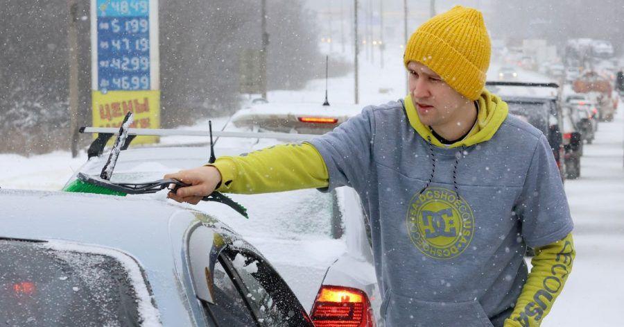 Kurz vor der Fahrt:Ein Mann wischt Schnee von seinem Auto.