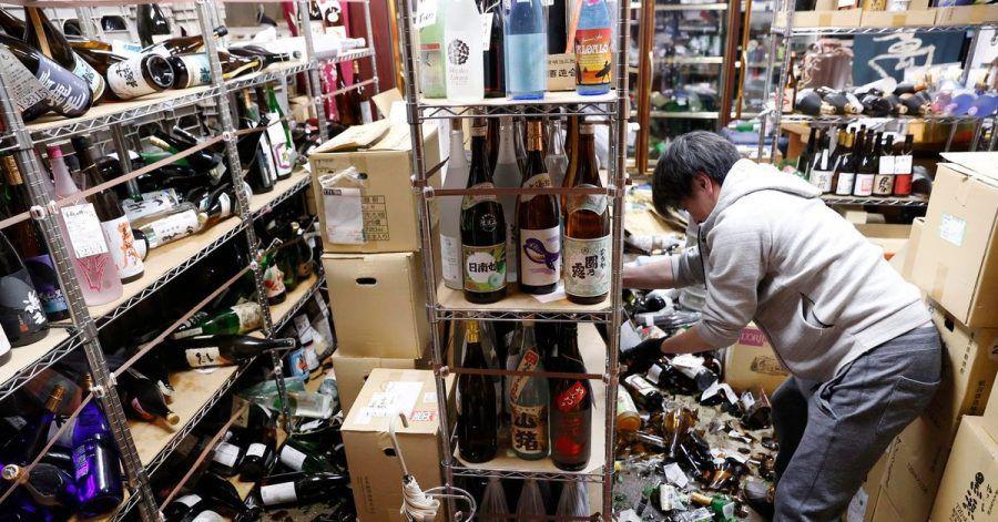 Der Inhaber eines Spirituosengeschäfts räumt nach einem starken Erdbeben in seinem Geschäft auf.