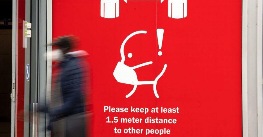 Ein Fussgänger geht an einem Schild vorbei, dass auf die Maskenpflicht hinweist. Die Einschränkungen zur Eindämmung der Coronavirus-Pandemie ziehen bis in den März.