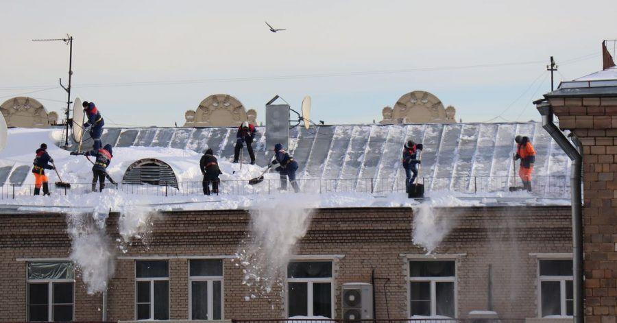 Menschen schaufeln Schnee vom Dach eines Mehrfamilienhauses in Moskau.