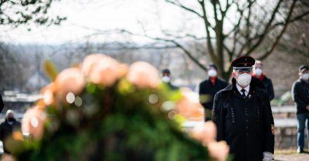 Ein Bergmann steht vor einem Kranz am Ehrenmal auf dem Friedhof in Bergkamen.