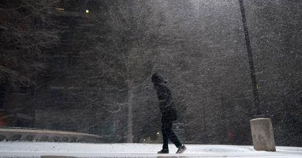 Eine Frau geht im texanischen San Antonio durch den fallenden Schnee.