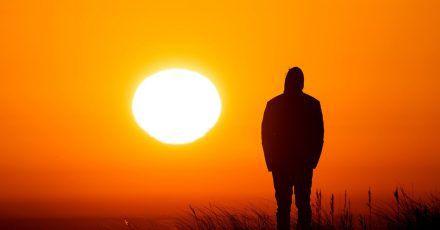 Ein Spaziergänger genießt am Strand von Schillig in Niedersachsen den Sonnenaufgang.