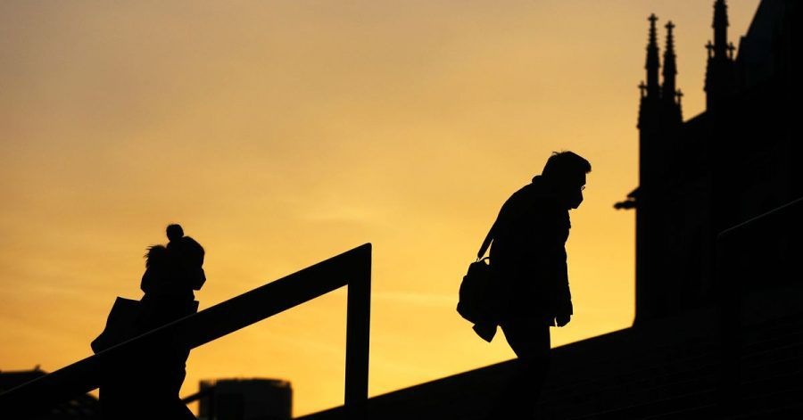 Menschen, die Schutzmasken tragen, gehen im Morgenlicht eine Treppe in Köln hinauf. Die sogenannte Sieben-Tage-Inzidenz in Nordrhein-Westfalen ist aktuell auf 61,7 gestiegen.