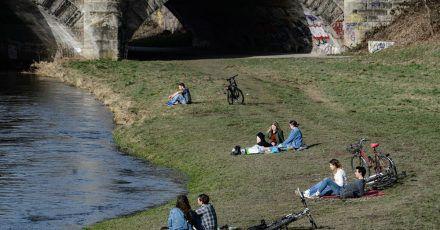 Junge Menschen genießen am Ufer der Leine in Göttingen das milde Wetter.