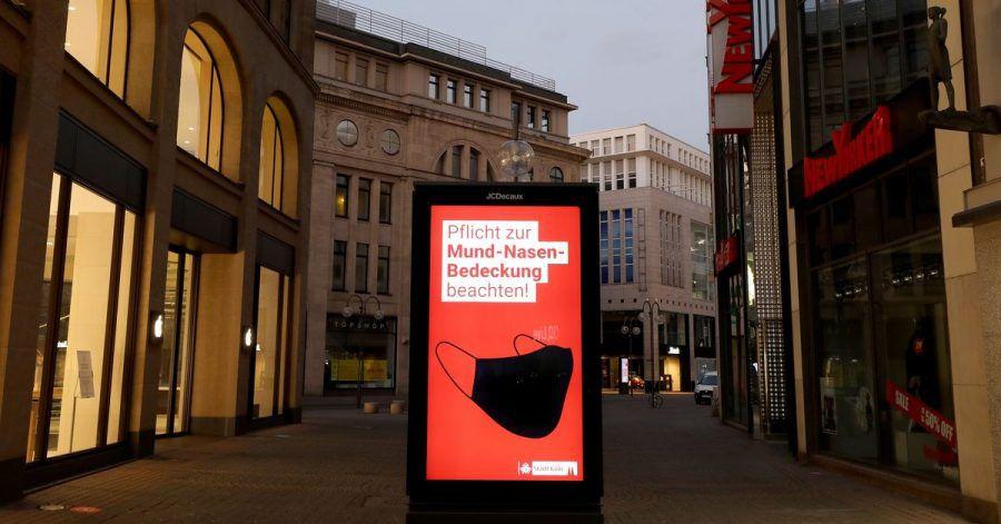 In der Kölner Fußgängerzone wird auf die Maskenpflicht hingewiesen.