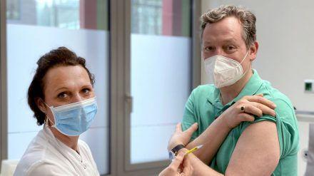 """""""Hirschhausen als Impfproband"""": Eckart von Hirschhausen lässt sich von Studienleiterin Professor Dr. Clara Lehmann (Uniklinik Köln) die Spritze setzen. (ili/spot)"""