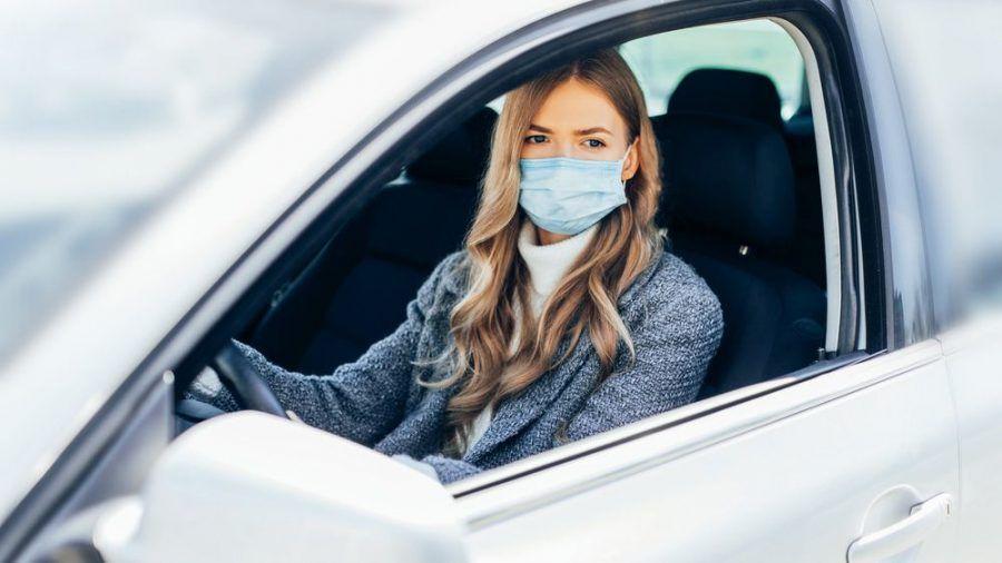 Eine junge Frau mit Schutzmaske im Auto (wue/spot)