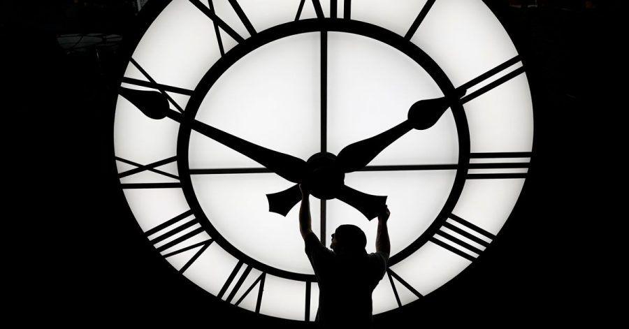 Ein Techniker bewegt die Uhrzeiger einer 500 kg schweren Uhr mit einem Durchmesser von mehr als 3,5 Metern.