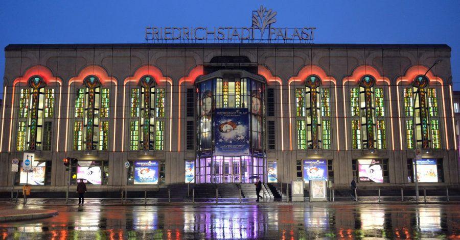 Die Beleuchtung des Friedrichstadt-Palastes wird während eines Regenschauers von der nassen Fahrbahn reflektiert.