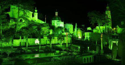 Das Dorf Portmeirion in Nordwales wird anlässlich des St. Patrick's Days grün beleuchtet. An mehreren Fassaden ist ein Kleeblatt abgebildet.
