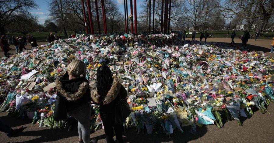 Zwei Frauen schauen sich die Blumen an, die für die getötete Sarah Everard im Clapham Common Park in London niedergelegt wurden.