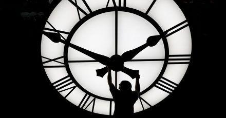 Ein Techniker bewegt die Uhrzeiger einer 500 kg schweren Uhr.