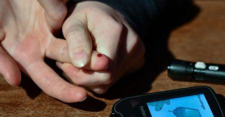 Ein Mädchen, das an Diabetes Typ 1 erkrankt ist, misst mit einem Blutzuckermeßgerät ihren aktuellen Zuckergehalt im Blut.