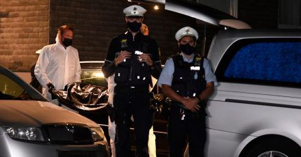 Mitarbeiter einer Beerdigungsfirma tragen eine Leiche unter Schutz von Polizisten zu einem Leichenwagen.