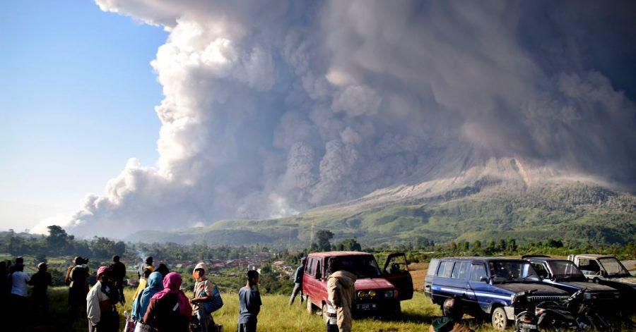 Menschen beobachten eine Eruption des Vulkans Sinabung.