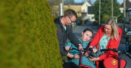 Vater David und Mutter Madeleine schnallen Vanessa auf dem Therapietandem an - dann drehen sie eine Runde durchs Dorf.