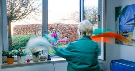 Übungsleiterin Babette Rackwitz-Hilke (l) von der TSV Reinbek macht Gymnastikübungen mit Tüchern vor, die Marianne Pinkus am Fenster wiederholt.