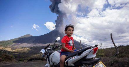Ein Kind sitzt auf einem Motorrad, während im Hintergrund der Vulkan Pacaya ausbricht.