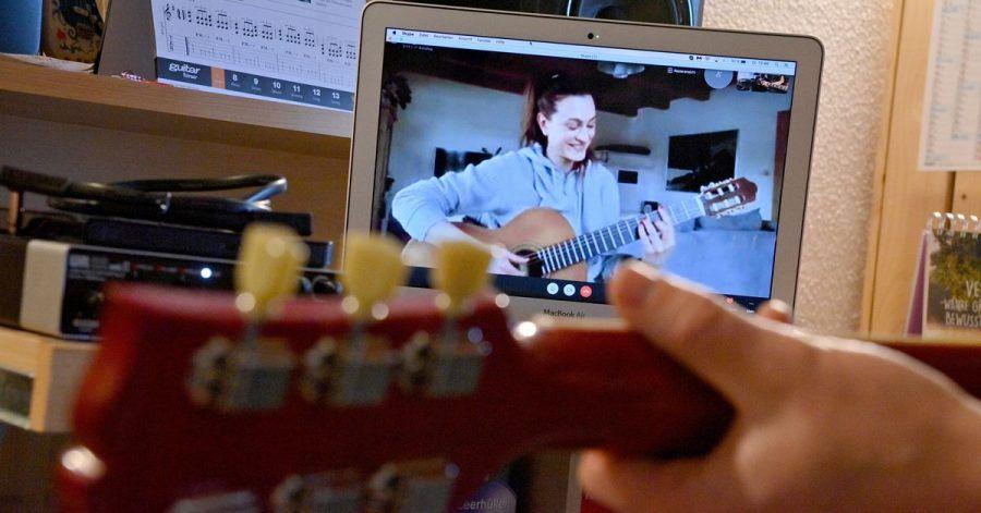 Ein Gitarrenlehrer unterrichtet eine Schülerin  via Online-Videokonferenz.