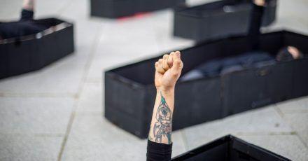 Frauen heben ihre Fäuste, während sie bei einer Demonstration im Vorfeld des Internationalen Frauentages vor dem Bundesgericht von Tel Aviv in Särgen liegen. Die Särge repräsentieren Frauen, die durch häusliche Gewalt getötet wurden.