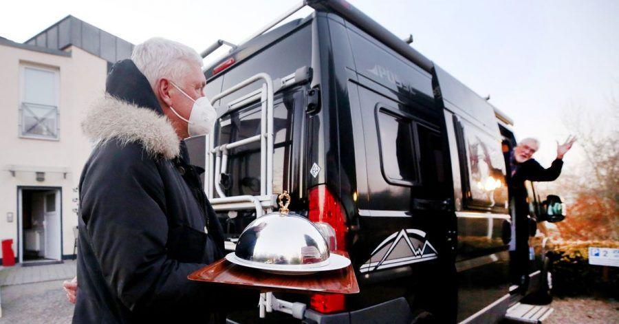 """Hans-Werner Scherer (l.), Gastwirt des Restaurantes Bootshaus Ruhreck"""", bringt seinem Kunden Hubert eine Vorspeise zu seinem Wohnmobil."""