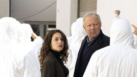 """""""Tatort: Borowski und die Angst der weißen Männer"""": Mila Sahin (Almila Bagriacik) und Klaus Borowski (Axel Milberg) inmitten der weißen Männer. (cg/spot)"""